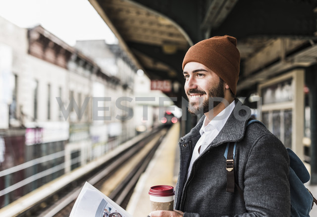 Young man waiting at metro station platform, holding disposable cup - UUF09029 - Uwe Umstätter/Westend61
