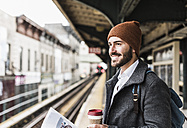 Young man waiting at metro station platform, holding disposable cup - UUF09029