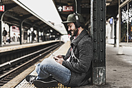 Young man waiting for metro at train station platform, using smart phone - UUF09032