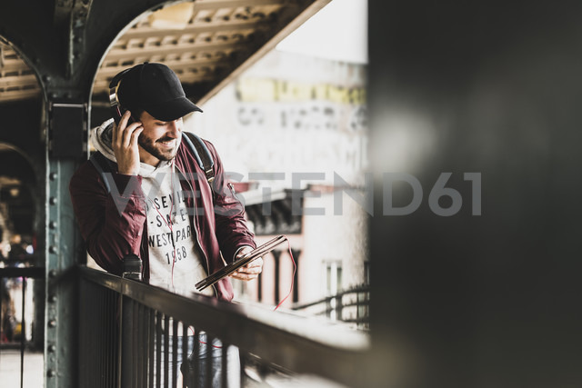 Young man waiting for metro, weraing headphones, using digital tablet - UUF09044