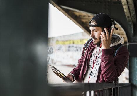 Young man waiting for metro, weraing headphones, using digital tablet - UUF09047