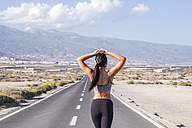 Young female athlete looking at road ahead - SIPF01021