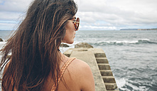 Woman with long brown hair standing on pier looking at distance - DAPF00452