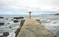 Back view of woman with arms outstretched standing on pier - DAPF00455