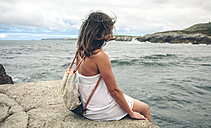 Woman with backpack sitting on pier looking at the sea - DAPF00458