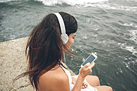 Woman listening music with headphones looking at smartphone in front of the sea - DAPF00464