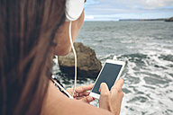 Woman using smartphone while listening with headphones in front of the sea - DAPF00467