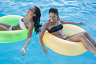 Two young women floating on water in swimming pool - MAUF00901