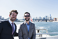 USA, New York City, two smiling businessmen on ferry on East River - UUF09050
