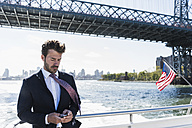 USA, New York City, businessman on ferry on East River checking cell phone - UUF09053