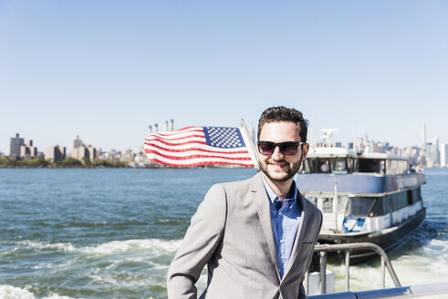USA, New York City, smiling businessman on ferry on East River - UUF09056