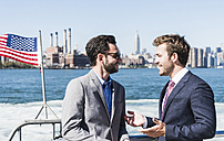 USA, New York City, two businessmen talking on ferry on East River - UUF09059