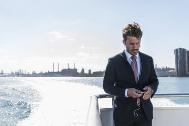 USA, New York City, businessman on ferry on East River with cell phone and earphones - UUF09062