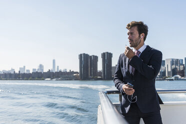 USA, New York City, businessman telephoning on ferry on East River - UUF09065