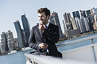 USA, New York City, businessman telephoning on ferry on East River - UUF09068