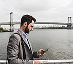 USA, New York City, businessman on ferry on East River checking cell phone - UUF09092