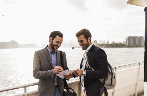 USA, New York City, two smiling businessmen with document on ferry on East River - UUF09095