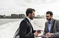 USA, New York City, two businessmen talking on ferry on East River - UUF09098