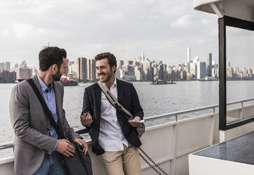 USA, New York City, two smiling businessmen talking on ferry on East River - UUF09104