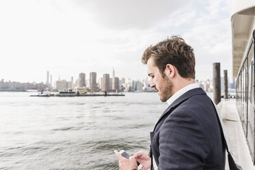 USA, New York City, businessman on ferry on East River checking cell phone - UUF09110