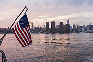 USA, New York City, US flag on ferry on East River with skyline of Manhattan in background - UUF09119