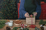 Woman decorating Christmas present, partial view - RTBF00497