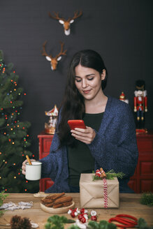 Smiling young woman with cup of coffee lokking at her cell phone at home - RTBF00500