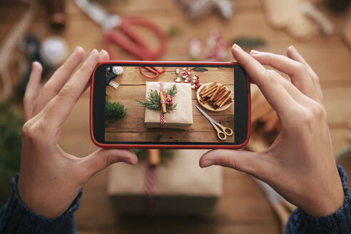 Woman photographing decorated Christmas gift  with smartphone, close-up - RTBF00503