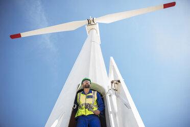 Engineer inspecting wind turbine, using wrench - ZEF11512