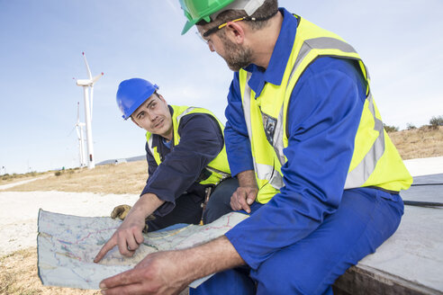 Engineers at wind farm looking at map - ZE11515