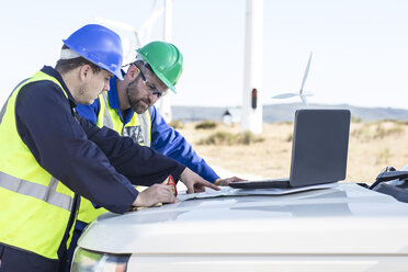Engineers at wind farm looking at map - ZEF11518