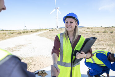 Female engineer shaking hands with colleagues on wind farm - ZEF11524