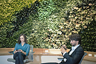 Business people using smart phones in front of green plant wall - WESTF21885