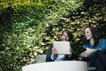 Businessman and woman sitting in front of green plant wall, using digital tablet - WESTF21891
