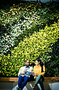 Businessman and woman sitting in front of green plant wall, using digital tablet - WESTF21900