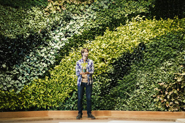 Young man standing in front of green plant wall, holding potted plant - WESTF21912