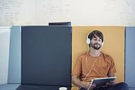 Casual businessman wearing headphones, using digital tablet - WESTF21930