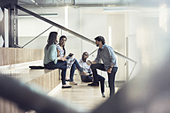 Young business people discussing, sitting on stairs - WESTF21948
