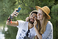Playful young couple at a lake taking a selfie - CRF02764