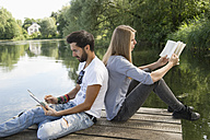 Young couple sitting on jetty at a lake with book and tablet - CRF02767