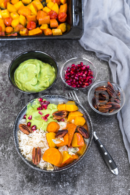 Bowl of autumnal salad with carrots, pumpkin, sweet potatoes, pecan, guacamole, pomegranate and rice - SARF03055