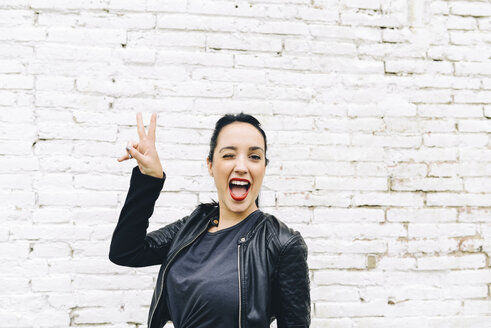 Portrait of young woman in front of brick wall making victory sign - GEMF01189