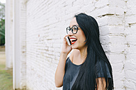 Happy young woman on cell phone in front of brick wall - GEMF01198