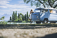Italy, Lake Garda, young woman drinking coffee at camping bus - SBOF00260