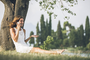 Young woman leaning against a tree talking on cell phone - SBOF00269