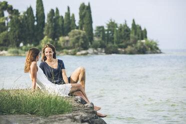 Italy, Lake Garda, two young women sitting at lakeshore - SBOF00275