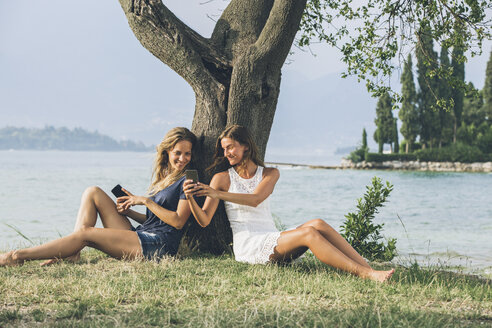 Italy, Lake Garda, two young women leaning against a tree using cell phones - SBOF00278