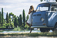 Italy, Lake Garda, young woman drinking coffee at camping bus - SBOF00287