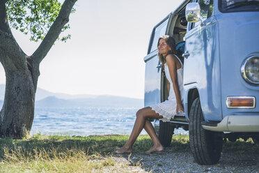 Italy, Lake Garda, smiling young woman in camping bus - SBOF00290