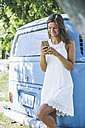 Smiling oung woman leaning against camping bus looking at cell phone - SBOF00293